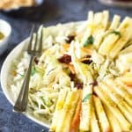Apples, cheese, cabbage, and raisins, in a bowl with a fork