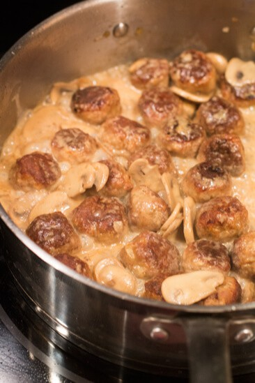 Meatballs in a mushroom sauce cooking on a stove