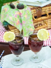 Cold drinks in glasses and a picnic basket