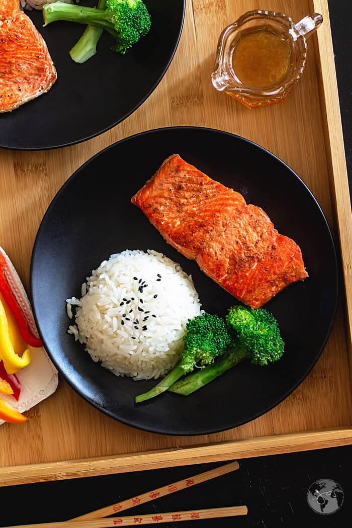 Salmon filet on a black plate with a round of rice