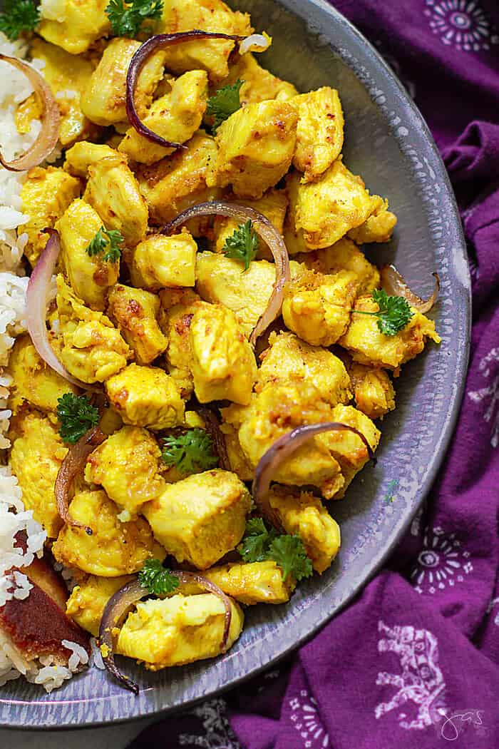An overhead close up shot of half the dish with bright yellow Indian chicken with purple towel as a background