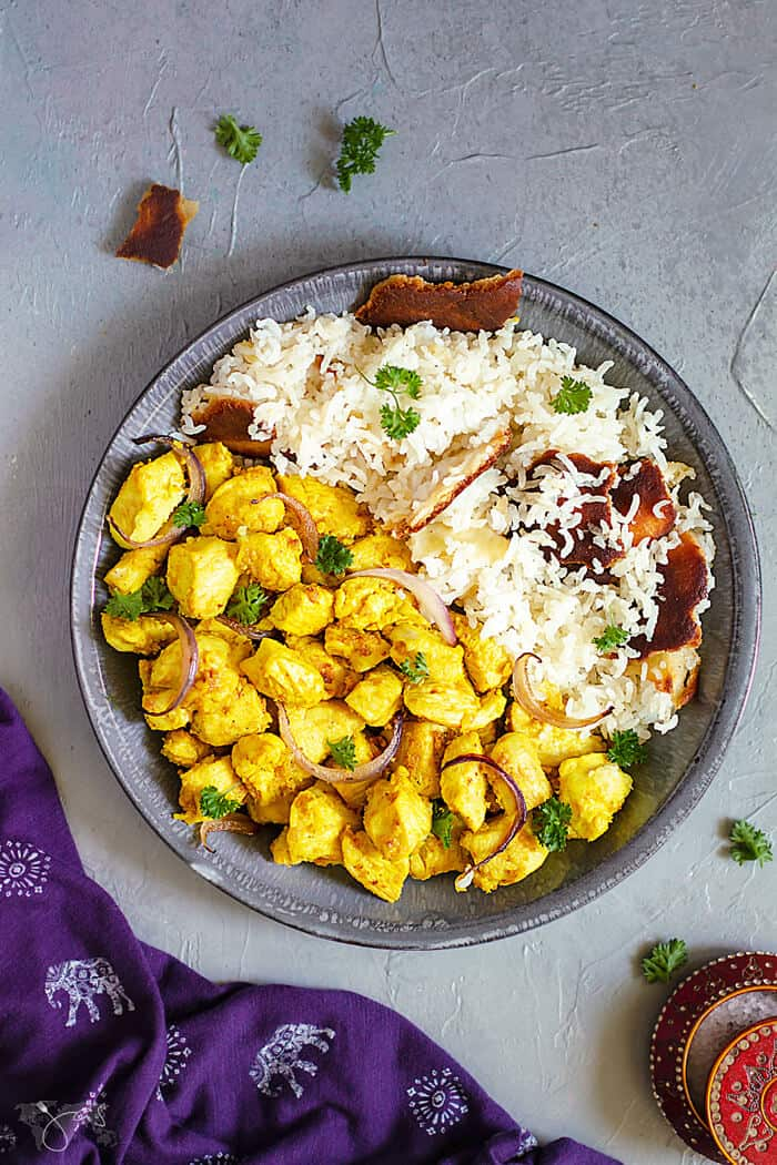 A flat lay of Indian chicken dish in a shallow gray bowl on one side and white rice on the other on a gray background and a purple towel
