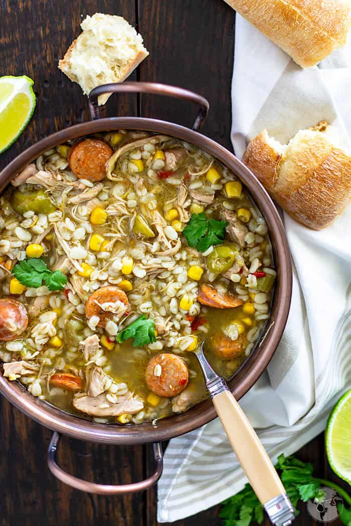 Gumbo soup in a copper bowl with a spoon and bread pieces.