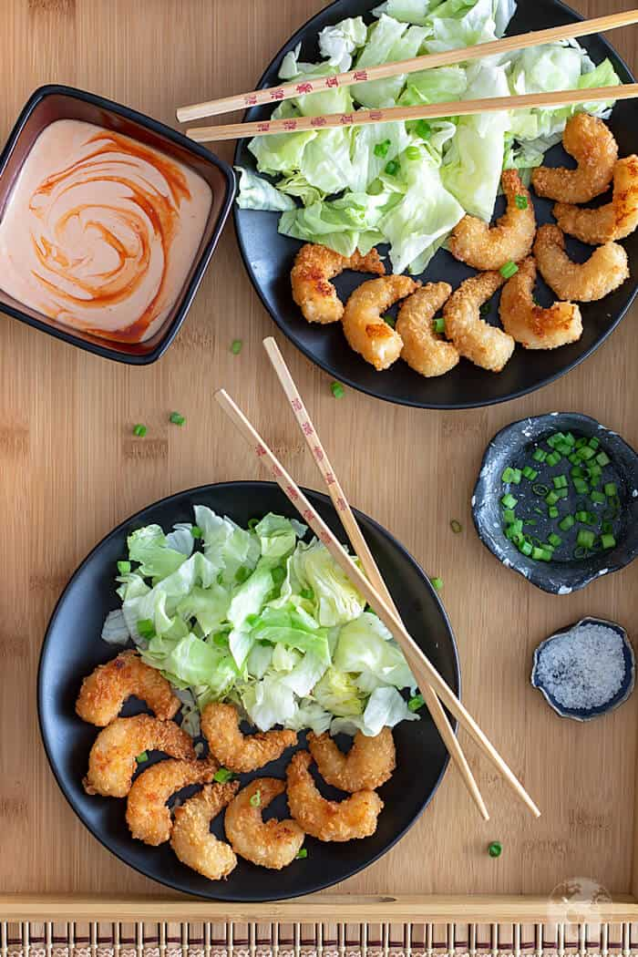 Overhead shot of two plates with shrimp, lettuce, sauce, and chopsticks on a wooden background.