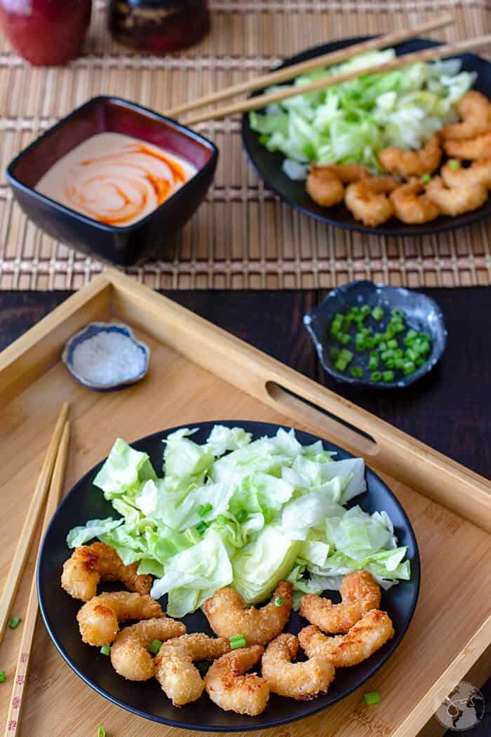 A wooden tray with plated bang bang shrimp and another plate in the background.