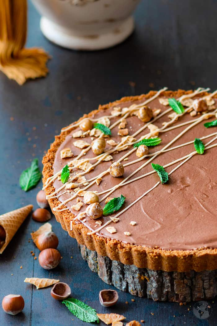 An angle shot of a mousse tart sprinkled with hazelnuts and mint leaves on a wooden plank.
