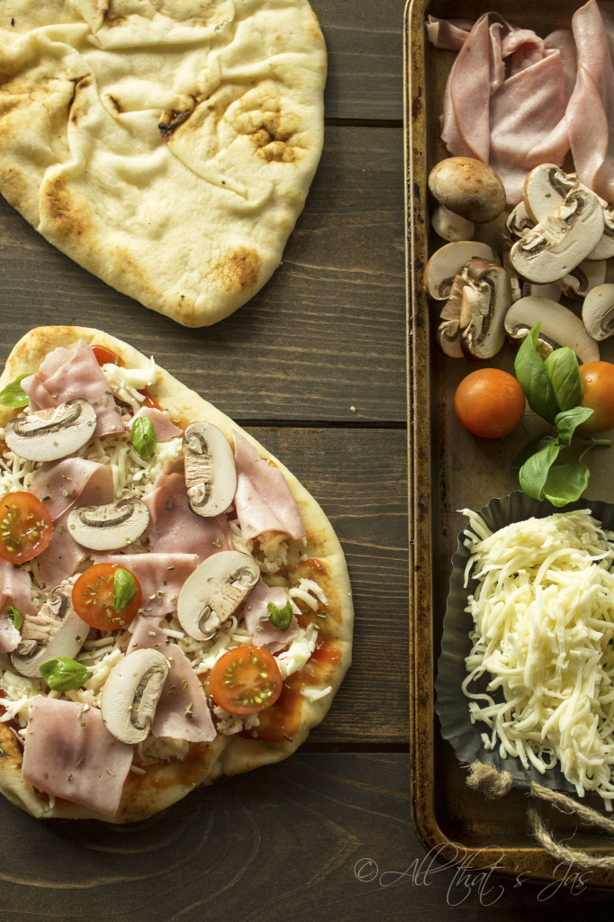 A bunch of food sitting on top of a wooden table, with Pizza and Naan
