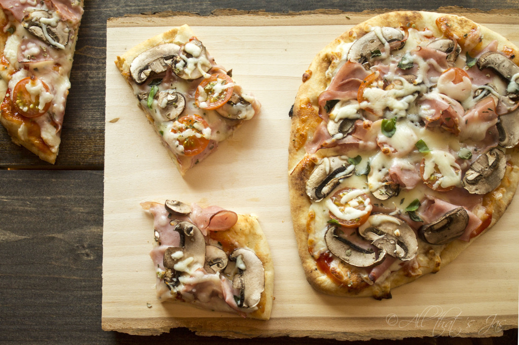 A slice of pizza sitting on top of a wooden cutting board, with Naan and Cheese
