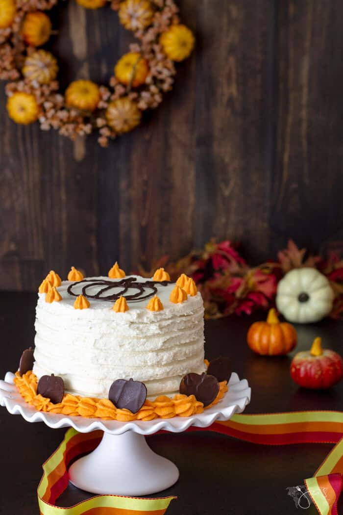 A straight shot of the pumpkin cake on a white cake stand with fall decoration in the background