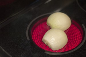 An onion cut in half on a hot stove plate