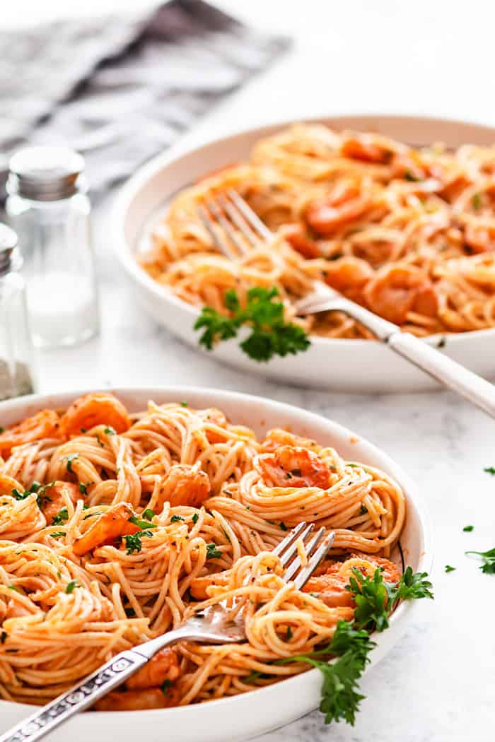 A shot of two plates with shrimp and pasta on a white background