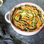 A bowl of sliced vegetables, with eggplant, tomato, and zucchini