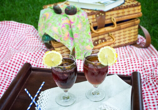 Two glasses with drinks at a picnic.