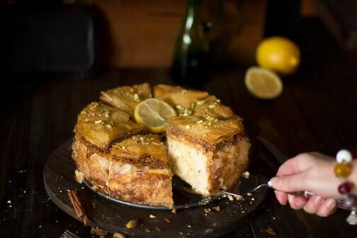 A person serving a piece of baklava cheesecake.