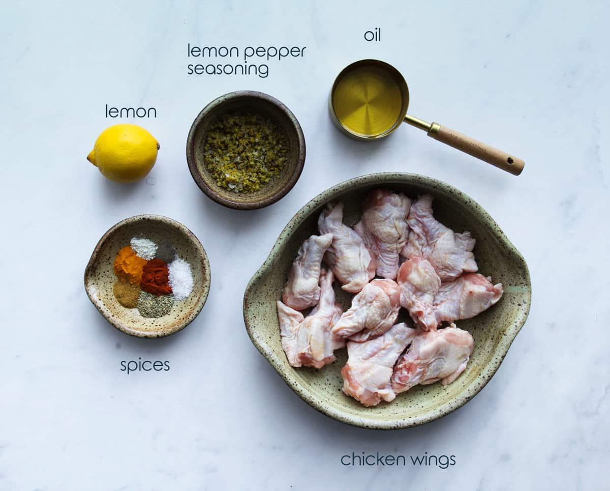 chicken wing sections, with spices and other ingredients for the recipe.