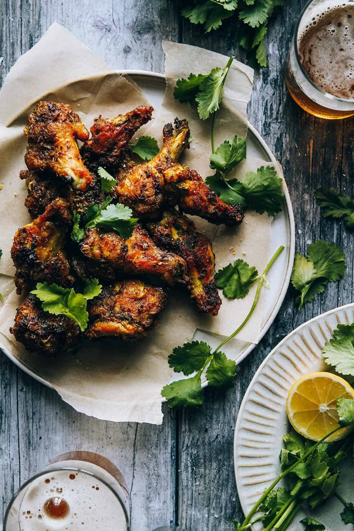 A flat lay of chicken wings on a plate sitting on a table with beer glasses.