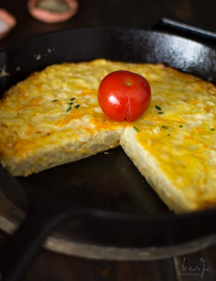 Frittata piece in a pan and tomato.