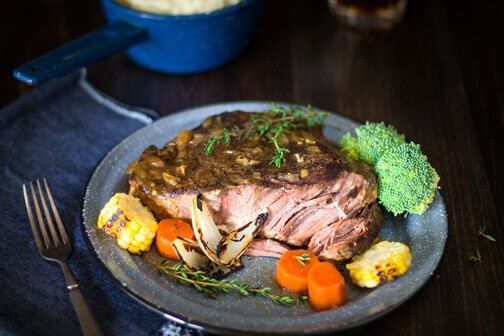 A plate with pot roast and vegetables.