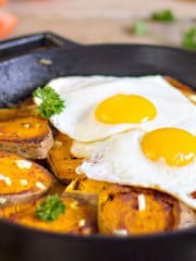 Potatoes and two eggs in a pan on a table