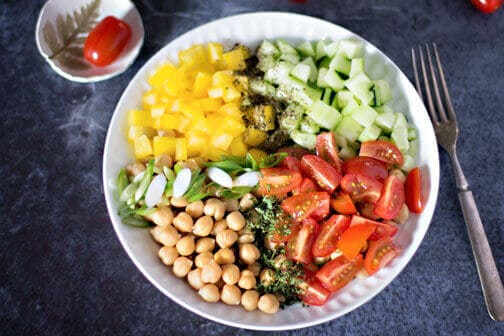 A bowl of chickpea salad with peppers and tomatoes