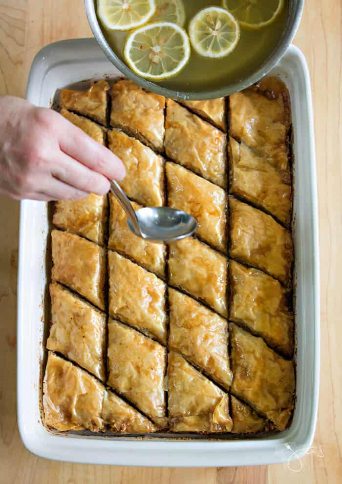 Pouring lemony syrup over baklava.