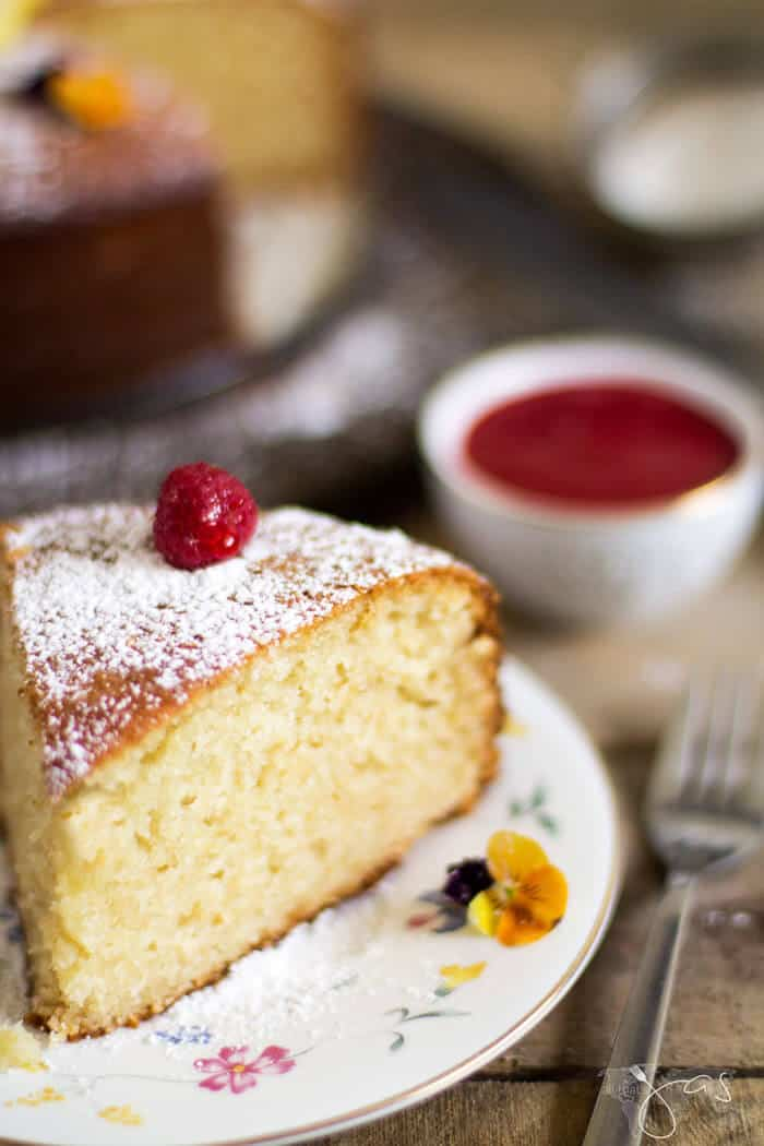 This delicious piece of lemon yogurt cake is moist and topped with a fresh raspberry.