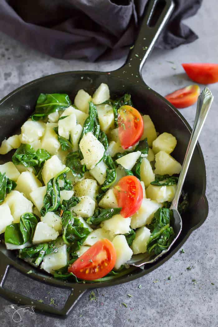 A cast-iron skillet with potatoes, Swiss chard, and tomatoes.