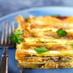 A slice of apple butternut squash lasagna on a blue plate with blue background.