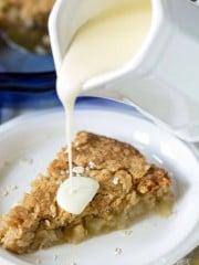 Homemade vanilla sauce being poured over warm apple pie.