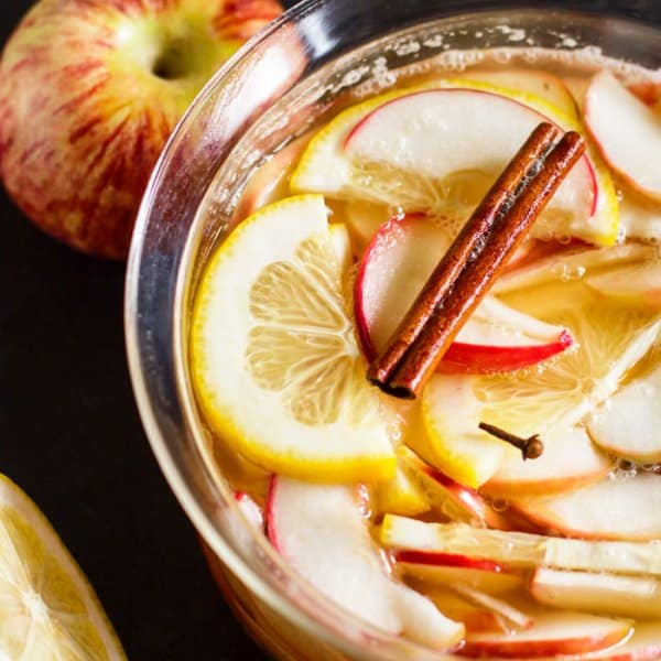 A pan with apples, lemon, and cinnamon sticks.