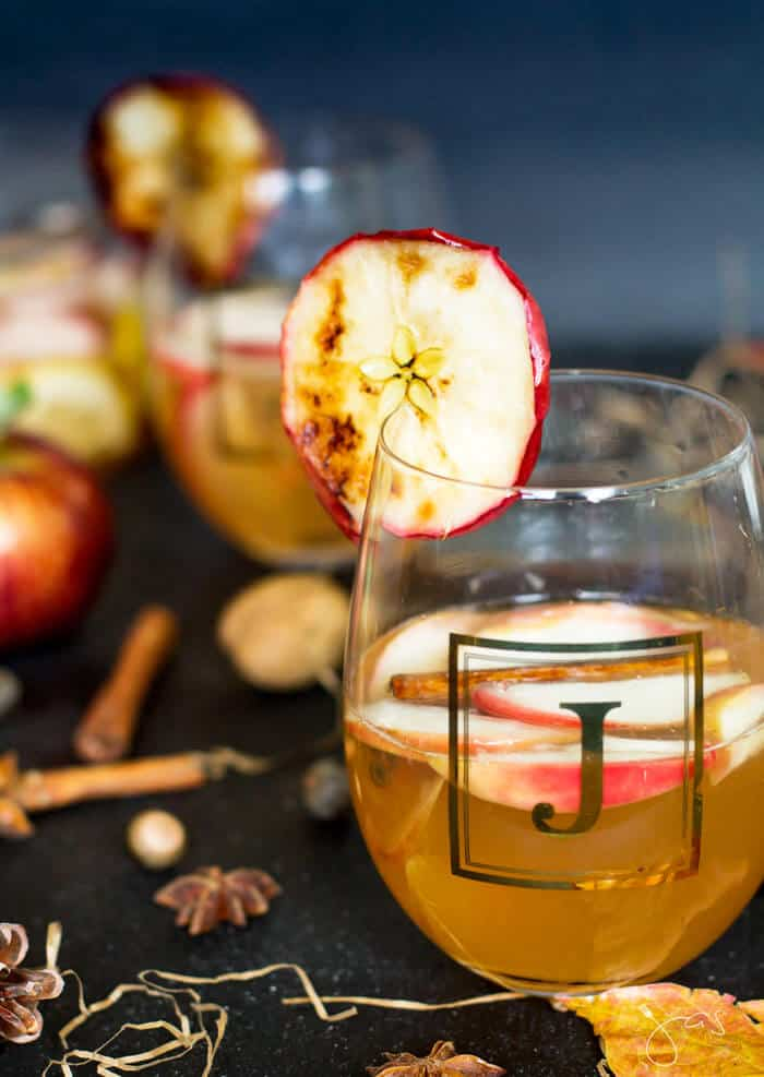 Apple punch with beer and spiced with cinnamon, cloves and lemon in a glass