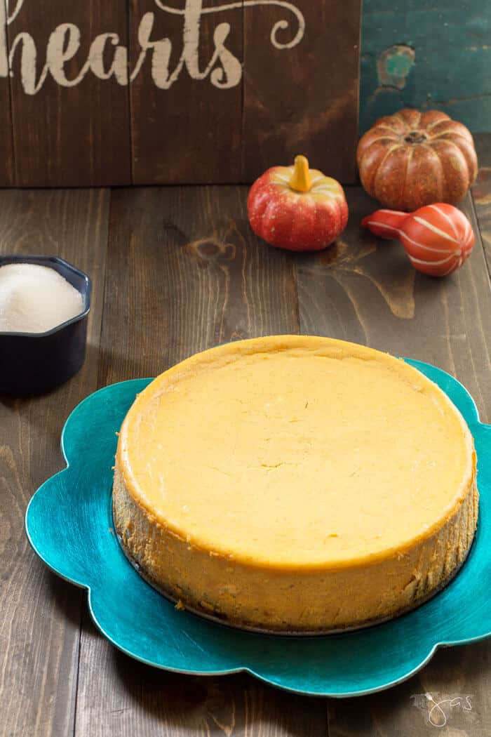 baked pumpkin cheesecake on a green platter and wooden background