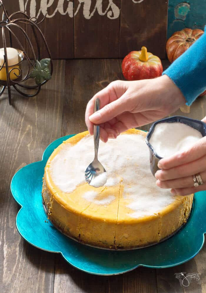 spreading caster sugar on the top of pumpkin cheesecake