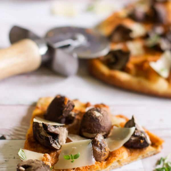 A slice of naan flatbread pizza with goat cheese and portobello mushrooms