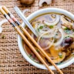 Japanese soup with onions and mushrooms in a bowl with chopsticks