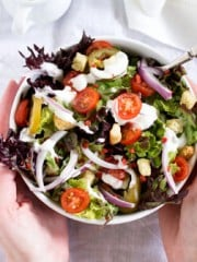 A person holding a bowl with salad on a table