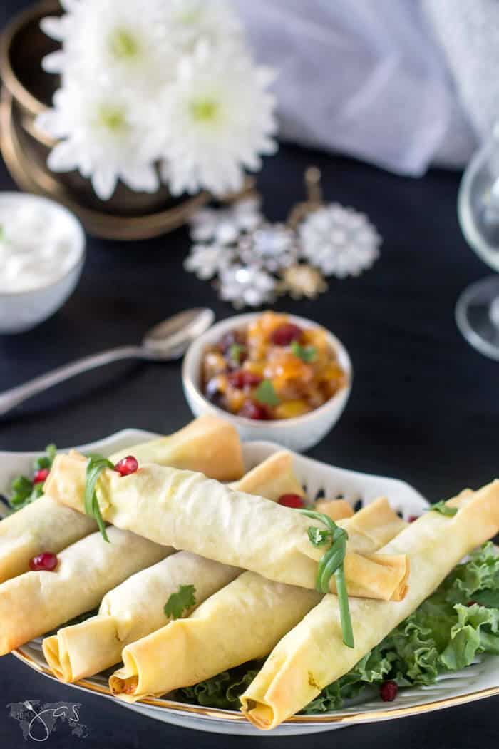 Fillo dough stuffed with spicy samosa on a plate sitting on the table with flowers and other food