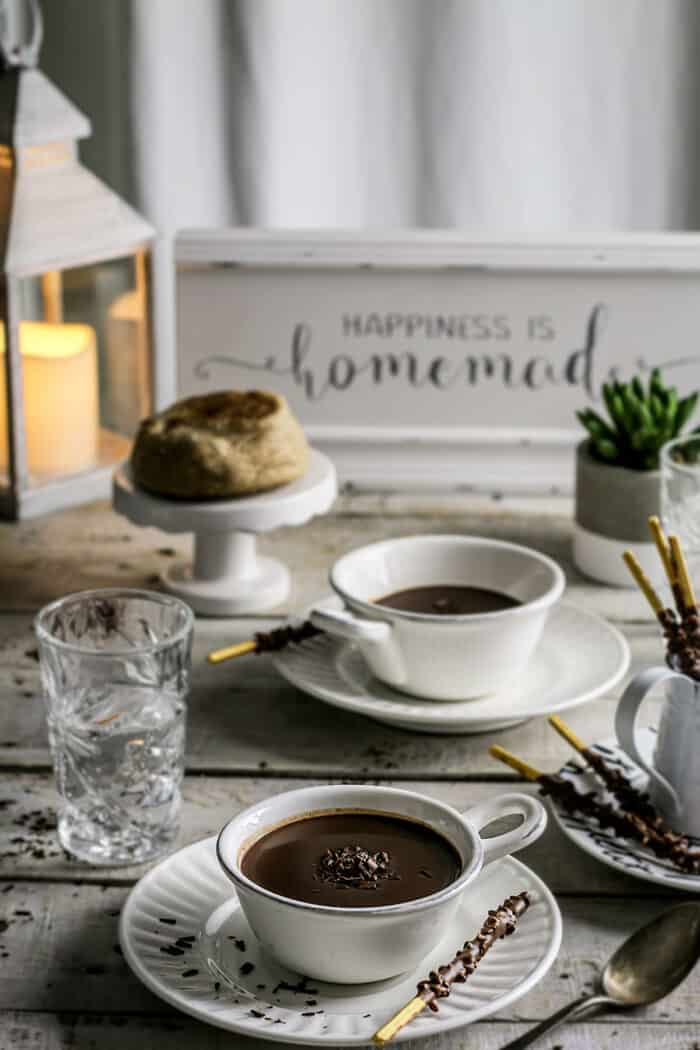 A rustic table setting with cups of hot chocolate.