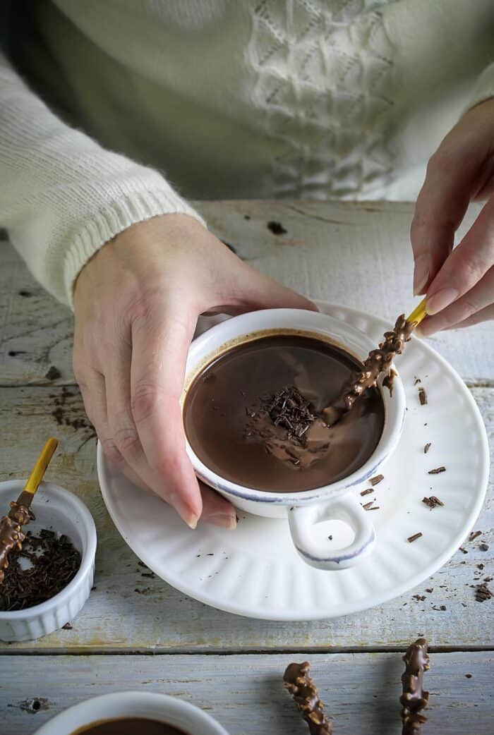 A hand holding the mug of hot chocolate and dipping chocolate stick.