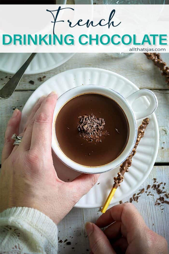 A hand holding the hot chocolate cup with text overlay