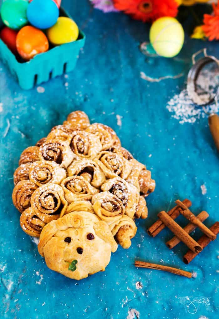 Cinnamon rolls in a shape of a lamb on a blue background.