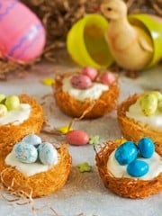 A bunch of pastry nests with candy eggs on top