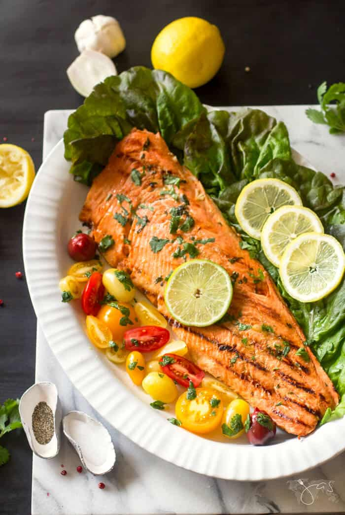 This delicious recipe for marinated salmon grilled to perfection is served with fresh tomatoes.