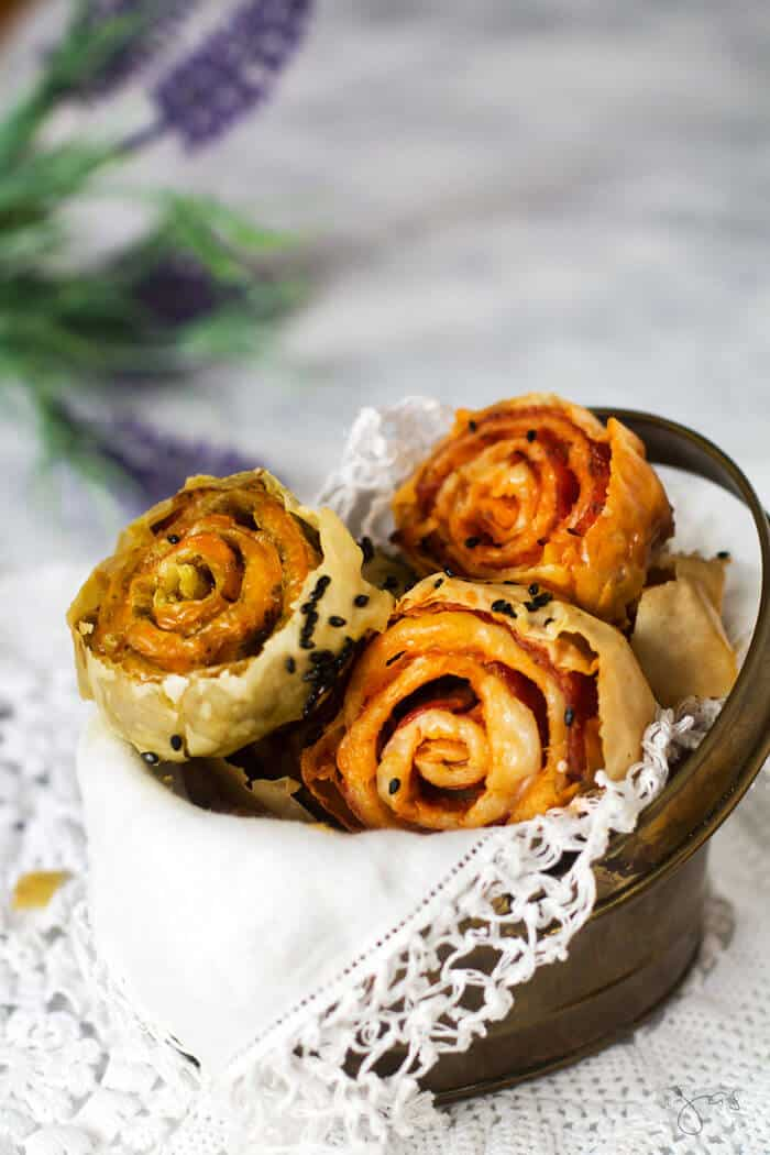 A close up of filled pastry pinwheels in a basket