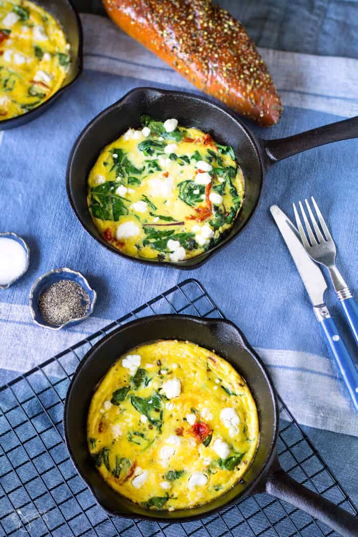 Three mini cast-iron skillets with frittata and bread on a blue tablecloth.