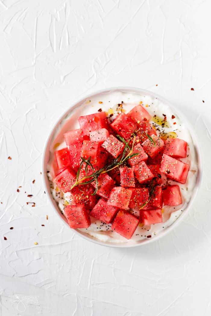 Overhead shot of watermelon salad on a white plate and white background.