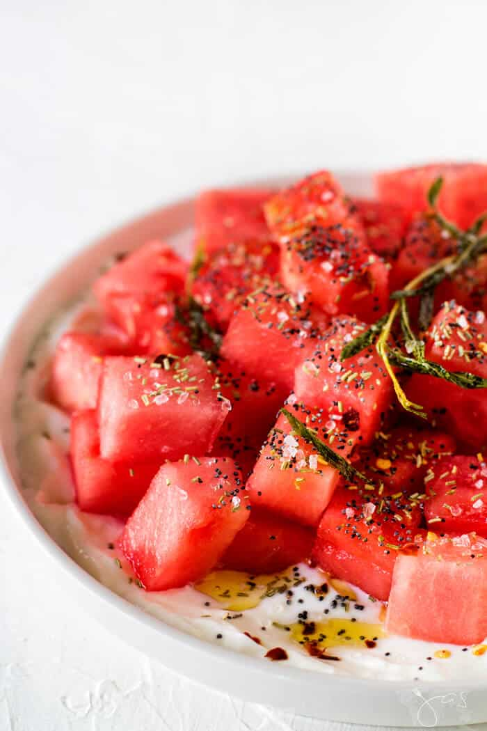 Israeli watermelon salad sprinkled with rosemary, oil, and poppy seeds.