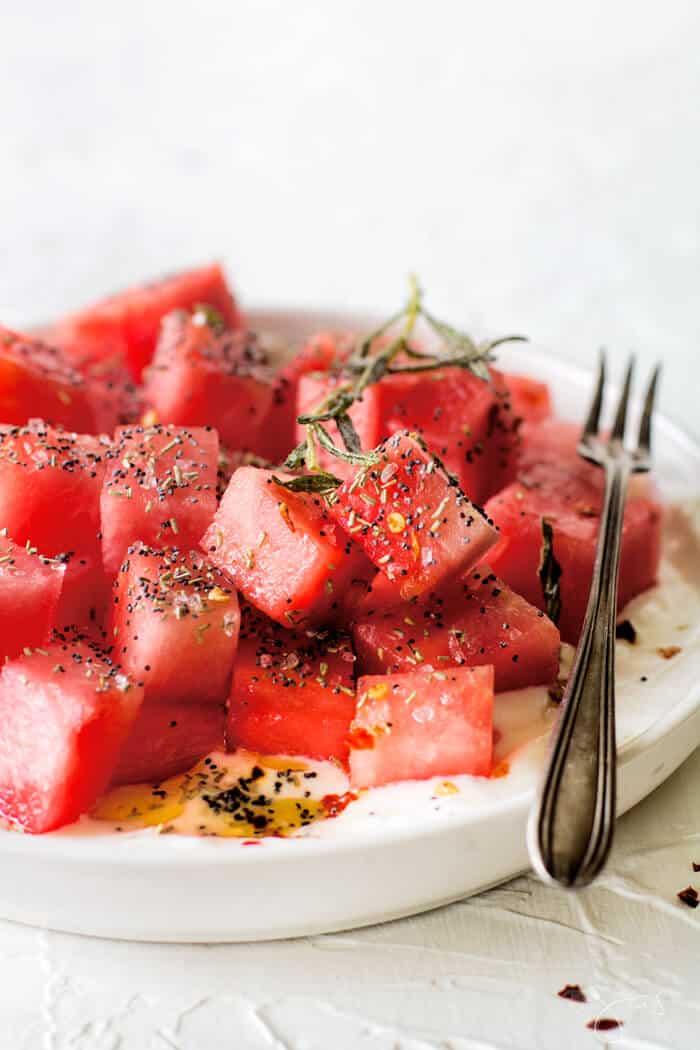 This refreshing Israeli Watermelon Yogurt Summer Salad with rosemary, crushed pepper flakes, poppy seeds, and mintis a little sweet, a little savory, little tart, and a whole lot delicious. | allthatsjas.com | #summer #salad #glutenfree #vegetarian #easy #fast #recipes #reicpeofthemonth #healthy #nutritios #potlucks #party #holidays
