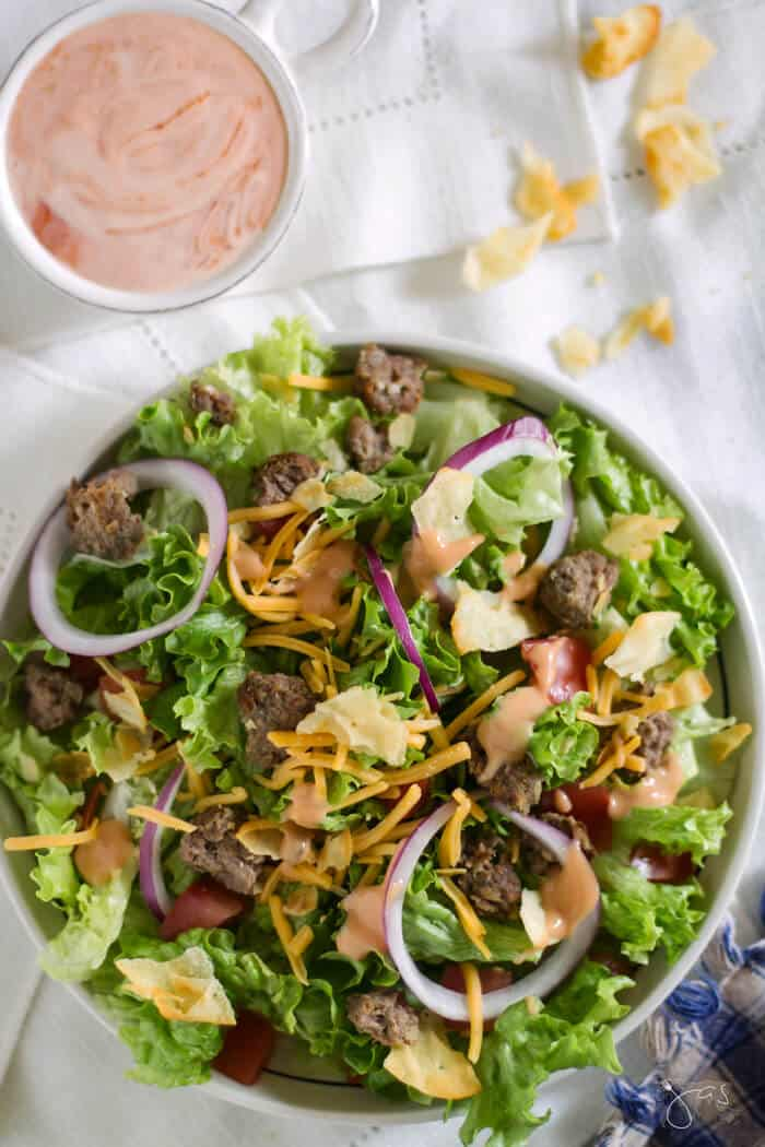 Fresh salad greens in a bowl with pieces of leftover burgers, cheese, chips, and onions with a small bowl of homemade dressing.