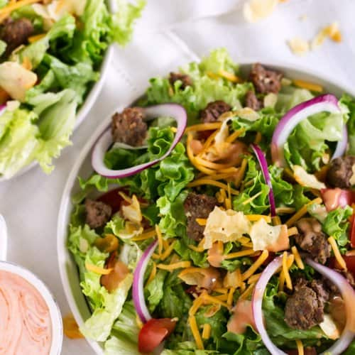An overhead shot of salad with leftover beef burgers on a white tablecloth.